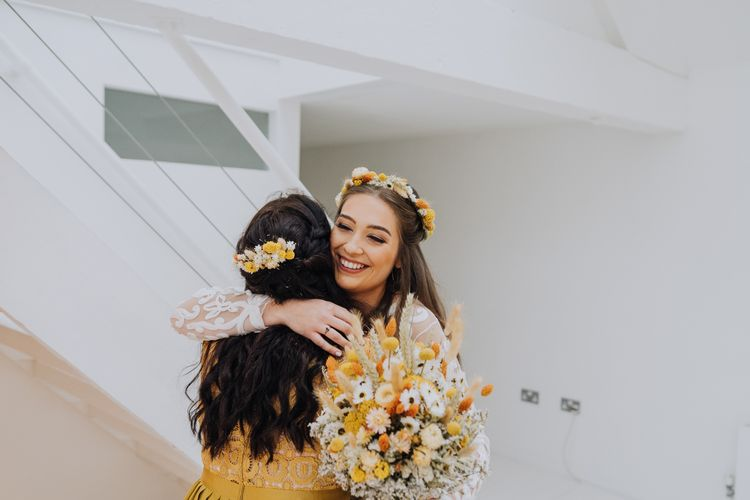 Bride hugging her bridesmaid in yellow dress
