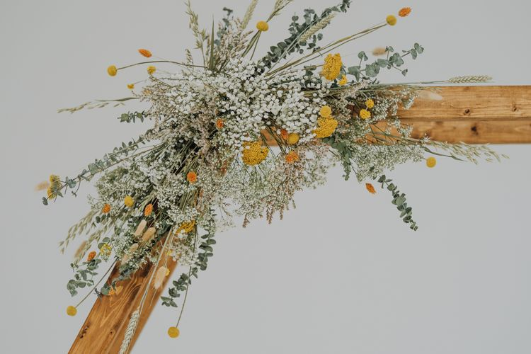 Hexagonal wooden frame decorated with dried flowers for minimalist yellow wedding theme