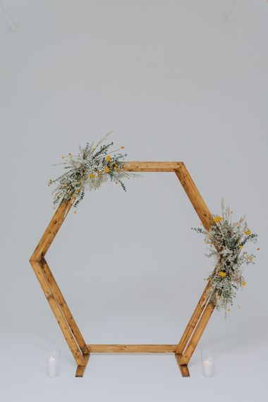 Hexagonal wooden altar with dried flowers for minimalist yellow wedding theme