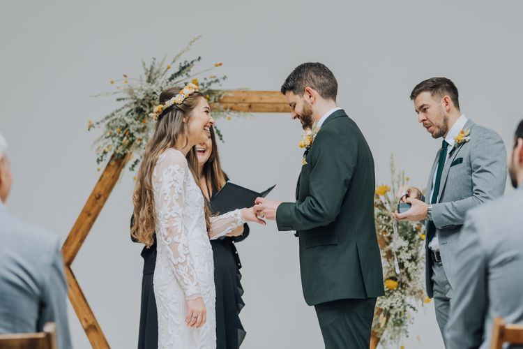 Bride and groom exchanging vows at minimalist wedding with yellow theme