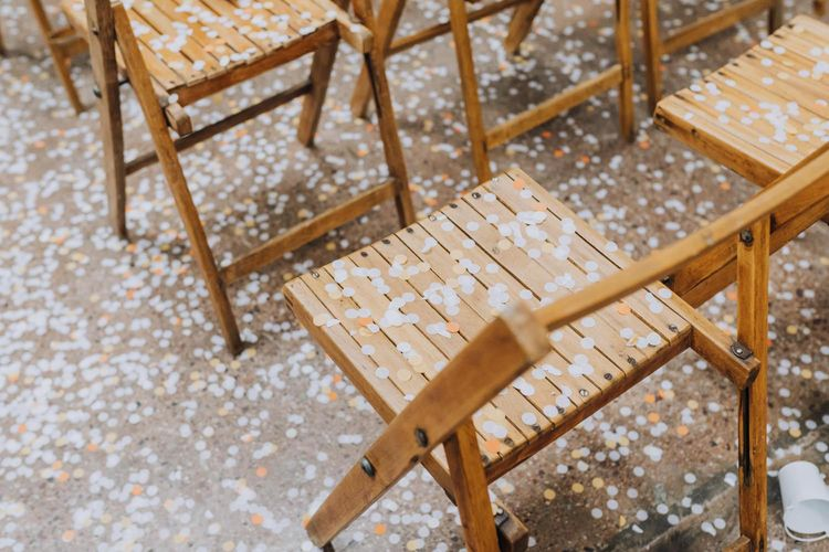 Wooden chairs covered in confetti for minimalist yellow wedding theme ceremony