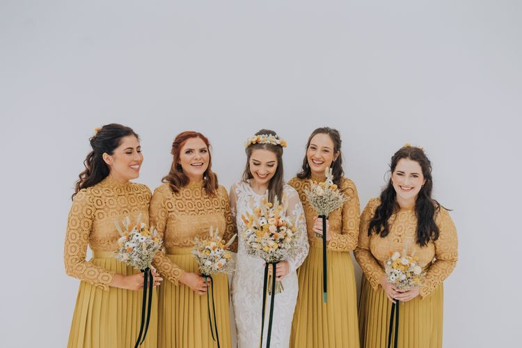 Bridal party portrait with bridesmaids in yellow dresses and bride in lace wedding dress for minimalist yellow wedding theme