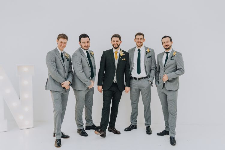 Groomsmen in grey suits at minimalist minimalist yellow wedding theme