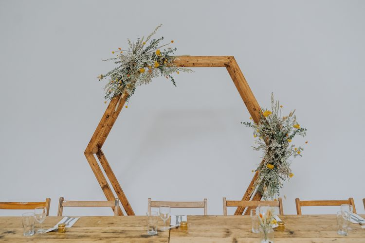 Hexagonal backdrop for top table with dried yellow flowers