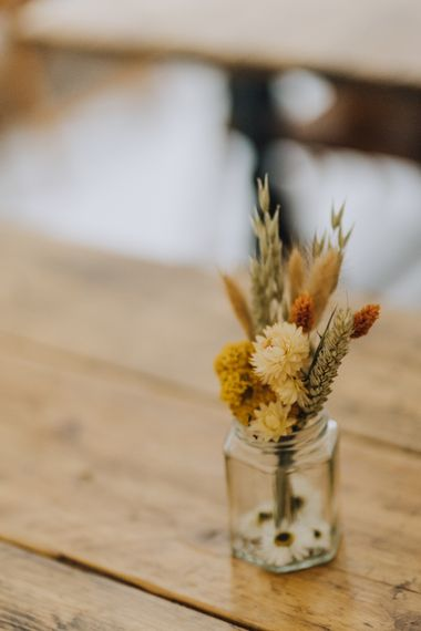 yellow dried flowers in jars for minimalist yellow wedding theme