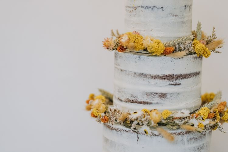 Semi naked wedding cake decorated with dried yellow wedding flowers