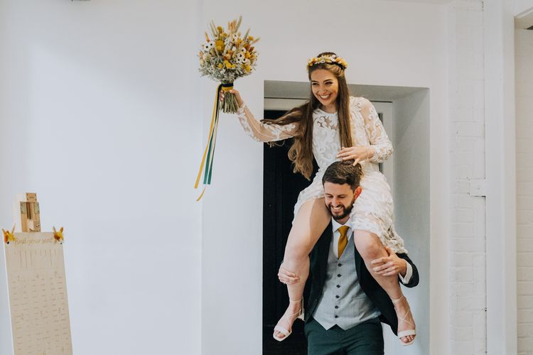 Bride entering the yellow themed wedding reception on her grooms shoulders
