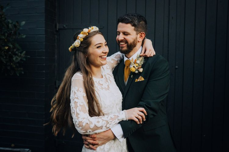 Groom embracing his bride in high street wedding dress and yellow flower crown