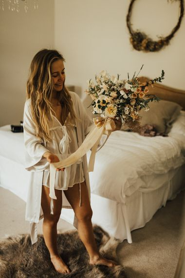 Bride Holding Wedding Bouquet of Mixed Flowers with Champagne Trailing Ribbon | Outdoor Ceremony at Fishley Hall with Grace Loves Lace Fringe Dress | Darina Stoda Photography