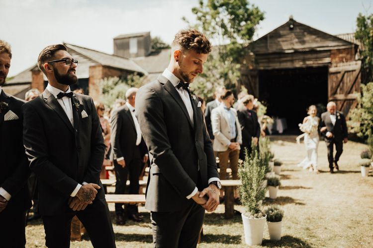 Wedding Ceremony | Arrival of the Bride | Groom in Black Gagliardi Suit with Bow Tie and Braces | Outdoor Ceremony at Fishley Hall with Grace Loves Lace Fringe Dress | Darina Stoda Photography