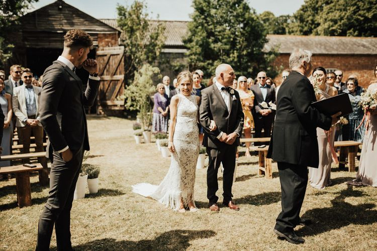 Entrance of the Bride | Bride in Embroidered Grace Loves Lace Gown with Fringing and Cut Out Back | Groom in Black Gagliardi Suit with Bow Tie and Braces | Outdoor Ceremony at Fishley Hall with Grace Loves Lace Fringe Dress | Darina Stoda Photography