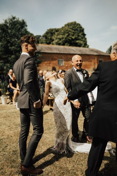 Bride Laughing with Groom and Father of the Bride | Bride in Embroidered Grace Loves Lace Gown with Fringing and Cut Out Back | Groom in Black Gagliardi Suit with Bow Tie and Braces | Outdoor Ceremony at Fishley Hall with Grace Loves Lace Fringe Dress | Darina Stoda Photography