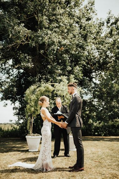 Wedding Vows | Wedding Arch Sculpted from Trees | Bride in Embroidered Grace Loves Lace Gown with Fringing and Cut Out Back | Groom in Black Gagliardi Suit with Bow Tie and Braces | Outdoor Ceremony at Fishley Hall with Grace Loves Lace Fringe Dress | Darina Stoda Photography