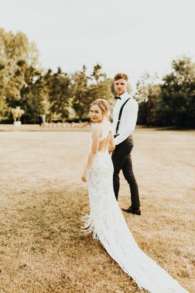 Bride in Embroidered Grace Loves Lace Gown with Fringing and Cut Out Back | Groom in Black Gagliardi Suit with Bow Tie and Braces | Outdoor Ceremony at Fishley Hall with Grace Loves Lace Fringe Dress | Darina Stoda Photography