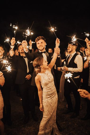 Sparkler Send Off | Bride in Embroidered Grace Loves Lace Gown with Fringing and Cut Out Back | Groom in Black Gagliardi Suit with Bow Tie and Braces | Outdoor Ceremony at Fishley Hall with Grace Loves Lace Fringe Dress | Darina Stoda Photography