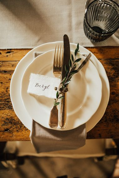 Place Setting | Wooden Trestle Tables with Grey Runner | Dove Grey Grey Napkin | Dark Grey Textured Glasses | Calligraphy Place Card | Outdoor Ceremony at Fishley Hall with Grace Loves Lace Fringe Dress | Darina Stoda Photography