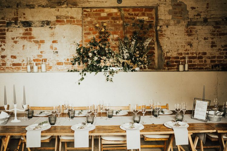 Wedding Reception Décor | Wooden Trestle Tables with Grey Runner | Grey Tapered Candles | Dark Grey Textured Glasses | Pillar Candles | Dove grey Napkins | Oversized Florals with Ochre and White Flowers and Foliage | Outdoor Ceremony at Fishley Hall with Grace Loves Lace Fringe Dress | Darina Stoda Photography