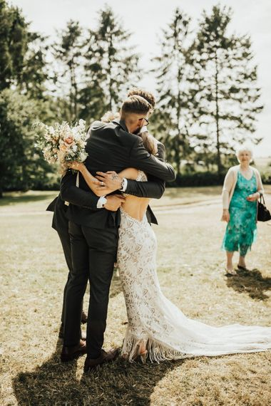 Bride in Embroidered Grace Loves Lace Gown with Fringing and Cut Out Back | Groom in Black Gagliardi Suit with Bow Tie and Braces | Bridal Bouquet of Mixed Ochre and White Flowers with Champagne Trailing Ribbon | Outdoor Ceremony at Fishley Hall with Grace Loves Lace Fringe Dress | Darina Stoda Photography