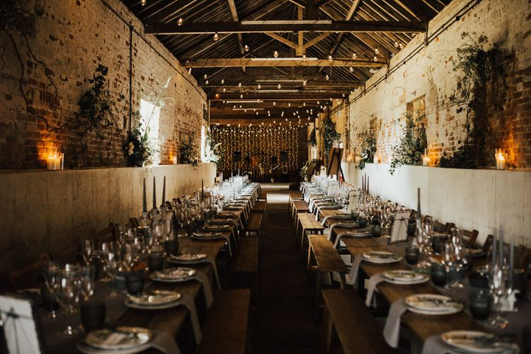 Wedding Reception Décor | Wooden Trestle Tables with Grey Runner | Grey Tapered Candles | Dark Grey Textured Glasses | Festoon Lights | Fairylight Canopy | Pillar Candles | Floral Wall Decoration | Outdoor Ceremony at Fishley Hall with Grace Loves Lace Fringe Dress | Darina Stoda Photography