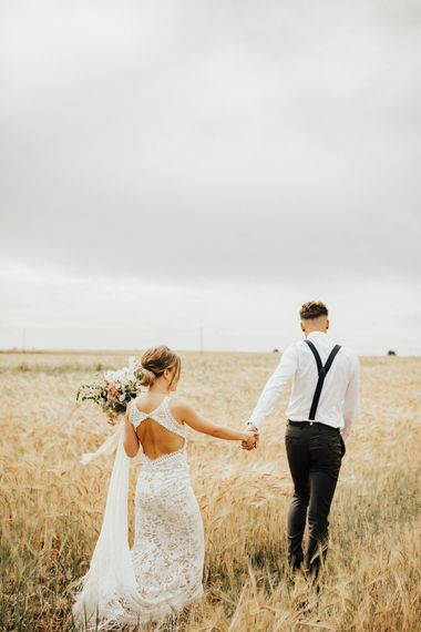 Bride in Embroidered Grace Loves Lace Gown with Fringing and Cut Out Back | Groom in Black Gagliardi Suit with Bow Tie and Braces | Bridal Bouquet of Mixed Flowers and Foliage with Champagne Trailing Ribbon | Outdoor Ceremony at Fishley Hall with Grace Loves Lace Fringe Dress | Darina Stoda Photography