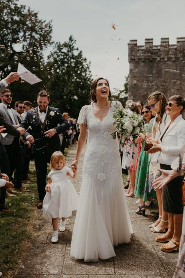 Confetti exit for bride with flower girl at church wedding