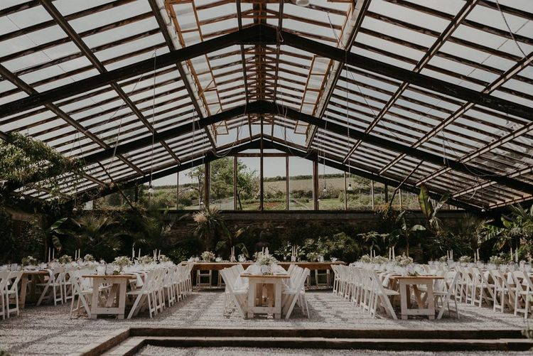 Glass house wedding venue with banquet tables