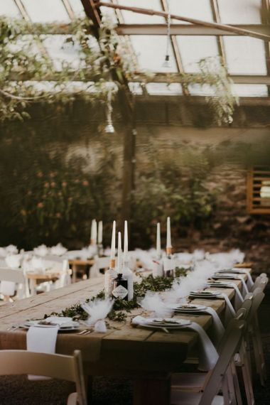 Wooden banquet tables with white flower decor and chairs