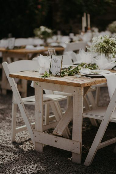 Wooden banquet tables with white flower decor and chairs and table numbers in frames