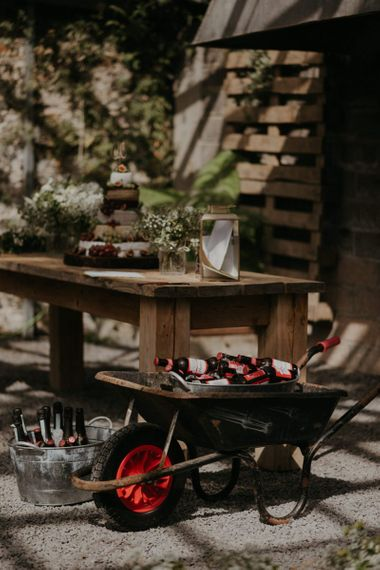 Rustic cake table with wheel barrow for beer