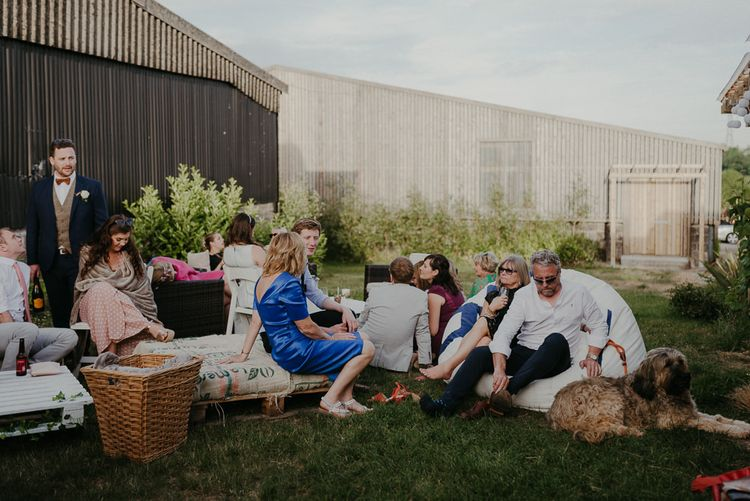 Guests and bridesmaids in beaded bridesmaid dresses relax in the venue gardens