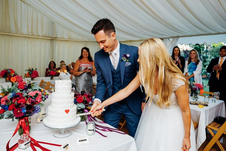 Cutting the Marks and Spencer Wedding Cake | Bride in Beaded Bodice Gown | Groom in Blue Reiss Suit | Bright DIY 'At Home' Outdoor Garden Ceremony & Marquee Reception | Marianne Chua Photography
