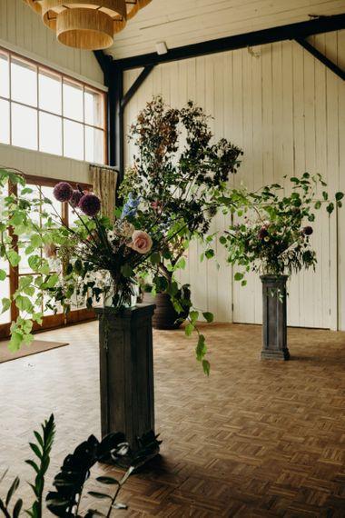 Wildflower arrangements on plinths at Soho Farmhouse Wedding