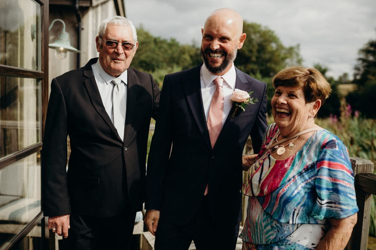 Groom in Navy Suit and pink Tie with his parents