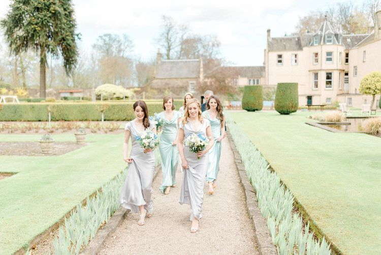 Bridesmaids in Grey and Green Ghost Satin Dresses  Walking Through the Wedding Venue Gardens