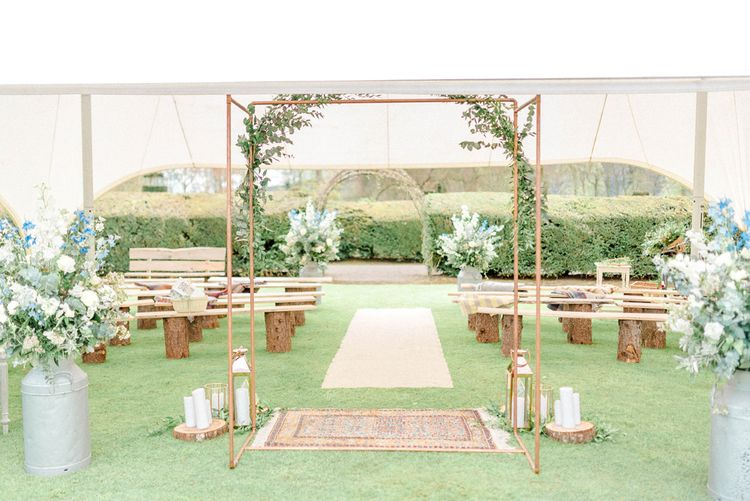 Wedding Ceremony Set up with Copper Fram Altar, Persian Rugs, Benches and Flower Filled Milk Churns