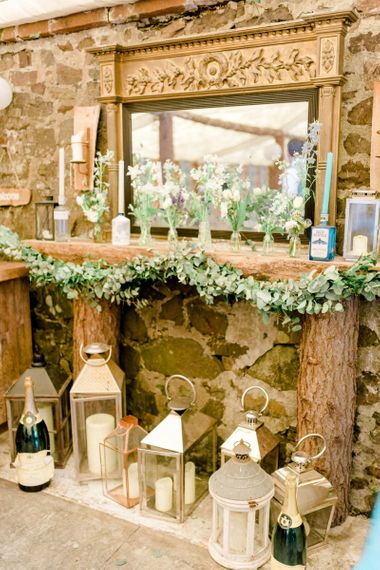 Faux Fireplace made of Logs with Mirror and Storm Lanterns Wedding Decor