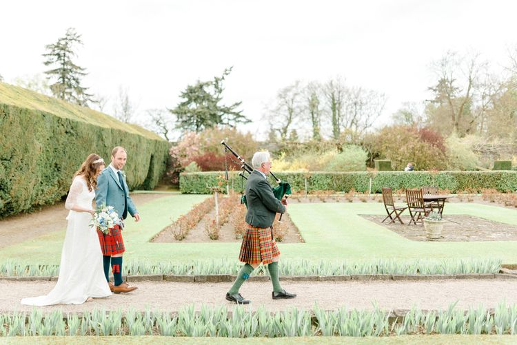 Bride and Groom Walking through the Wedding Venue Gardens Lead by a Bag Piper