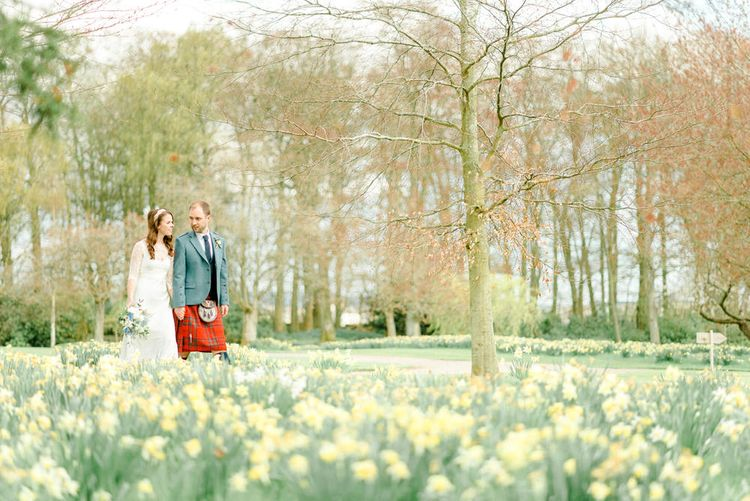 Bride and Groom Walking Through a Bed of Daffodils