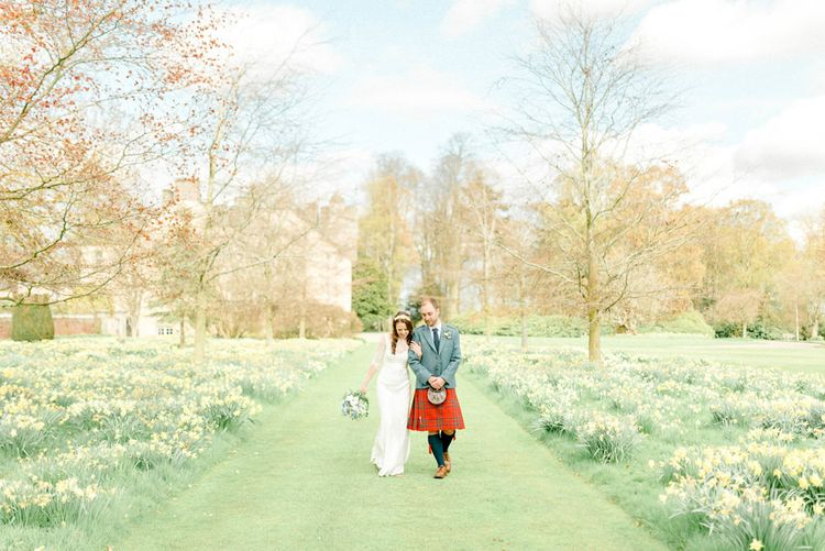 Bride and Groom Walking Through the Wedding Venue Gardens with Daffodil Patches Either Side