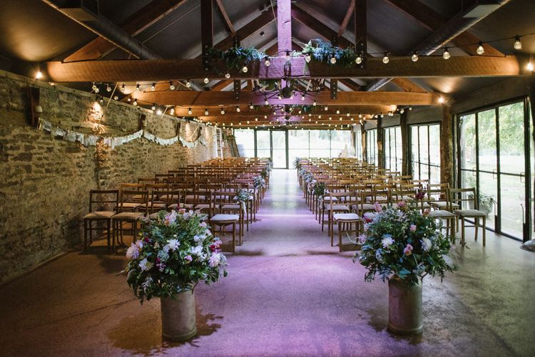 Barn Wedding Ceremony Venue with Two Milk Churns at the Altar Filled with Flowers