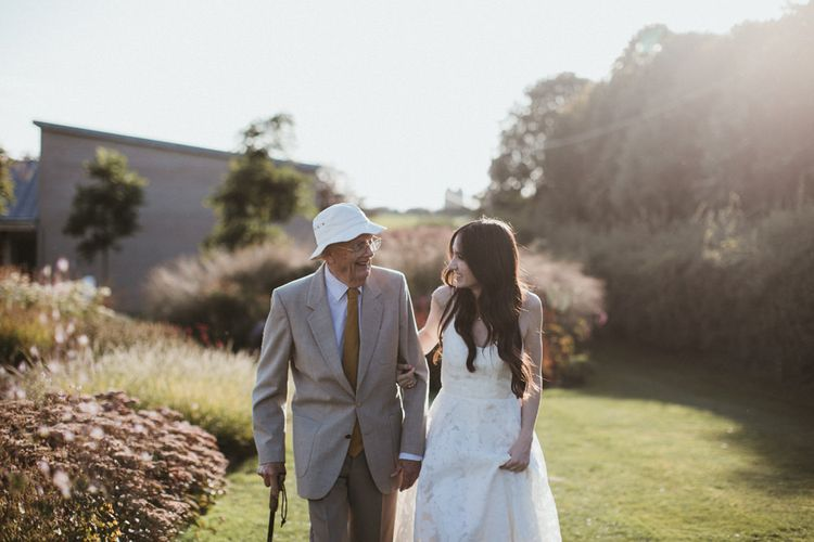 Bride Strolls Through Venue Grounds With Guest