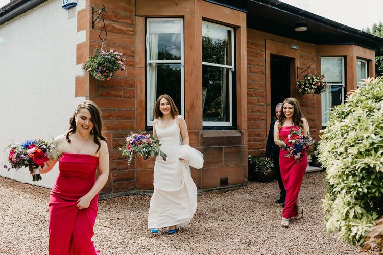 Bride and bridesmaids in red dresses leaving the house
