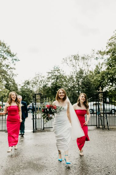 Bride and bridesmaids in red dresses entering the church