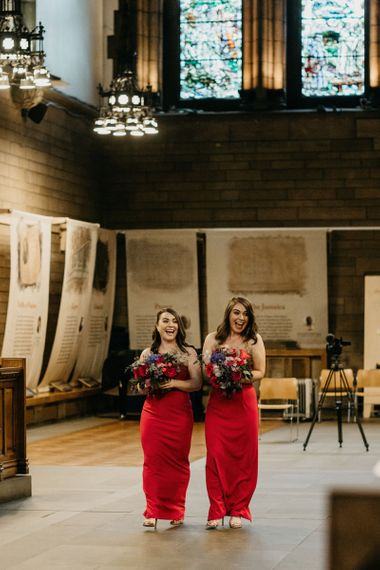 Bridesmaids in red dresses walking down the aisle