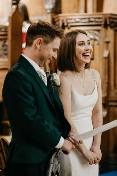 Bride and groom laughing at Glasgow University Chapel  wedding ceremony