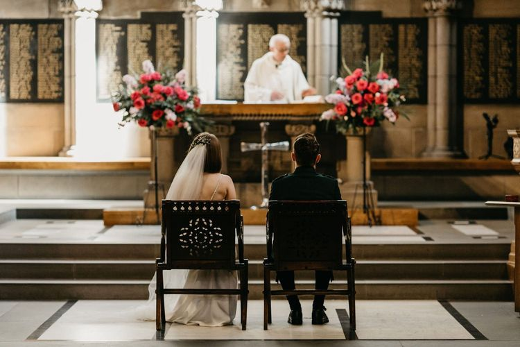Bride and groom sitting at the altar at Glasgow University Chapel  wedding ceremony