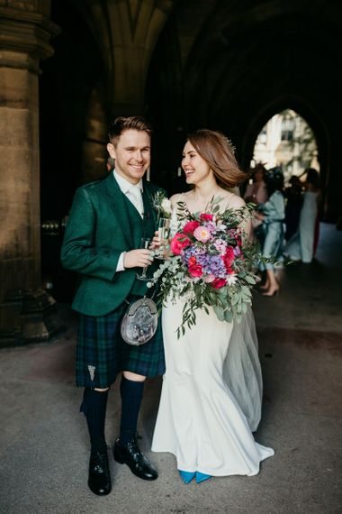 Bride and groom portrait with groom in tartan kilt and bride holding a colourful wedding bouquet