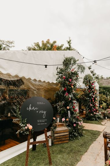 Marquee reception with round black welcome sign