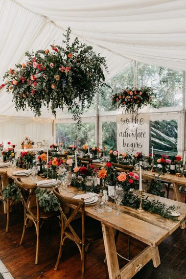 Socially distanced marquee reception with colourful flower decor
