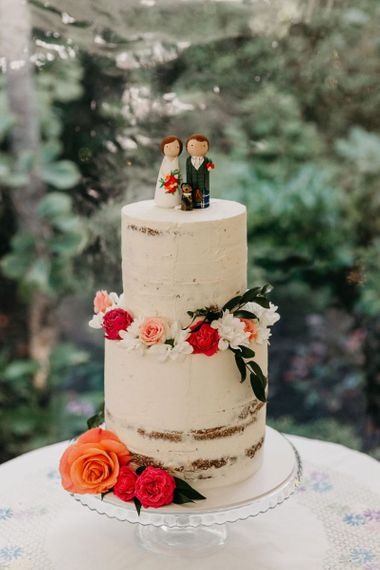 Semi naked wedding cake with people cake topper